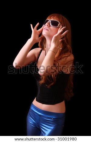 Young red head woman with sunglasses on black background - stock photo