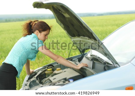 young redhead curly girl with broken down car with hood open call for help. woman stand against green grass or wheat field  - stock photo