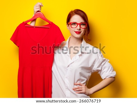 Young redhead designer with red dress on yellow background