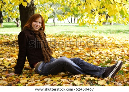 young redhead girl in warm clothes sitting near autumn tree, smiling and looking at camera - stock photo