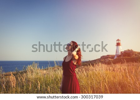 young redhead girl with sunglasses near Lighthouse and blue sea on background - stock photo