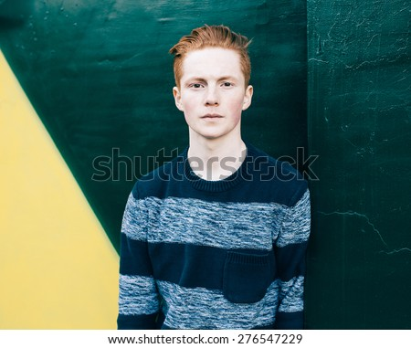 Young redhead man in a sweater and jeans standing next to green and yellow wall - stock photo