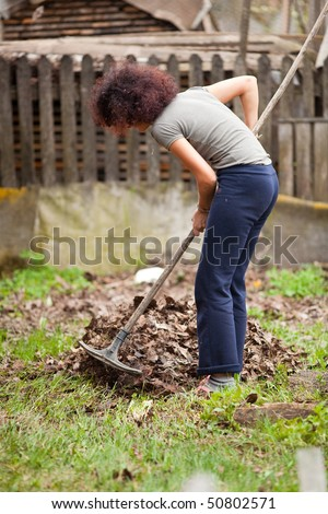 Young redhead pretty country girl using a rake to clean up of the fallen leaves