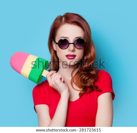 Young redhead student girl in red dress with toy ice-cream on blue background. - stock photo