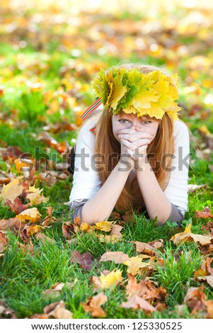 young redhead teenager woman in a wreath of maple leaves lying on the grass - stock photo