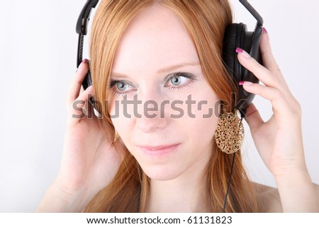 Young redhead with headphones - stock photo