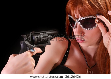 Young redhead woman and gun to her face - stock photo
