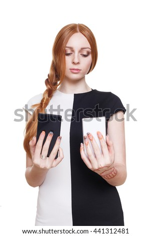 Young redhead woman choose between two cell phones. Girl looks at mobile, selecting color - black or white. Comparing smartphones in her hands. Female portrait isolated at white background - stock photo