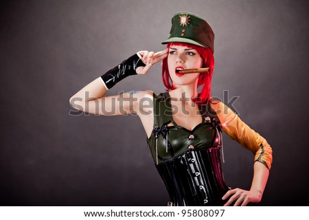 Young redhead woman dressed in military style latex and green cap, studio shot - stock photo