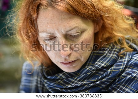 young redhead woman feeling bad and looking down with negative facial  expressions blurred background  - stock photo