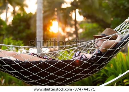 Young redhead woman in a bikini relaxing in a hammock in sunset time  - stock photo