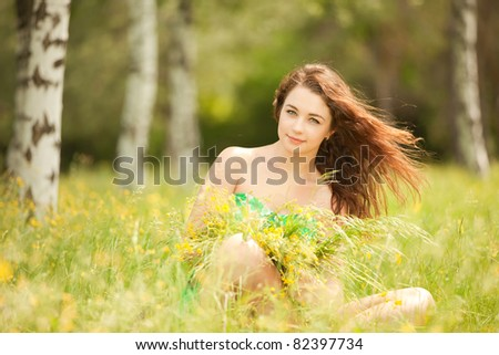 Young redhead woman in the park with flowers - stock photo