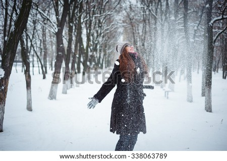Young redhead woman in winter park having fun with snow falling in hands - stock photo