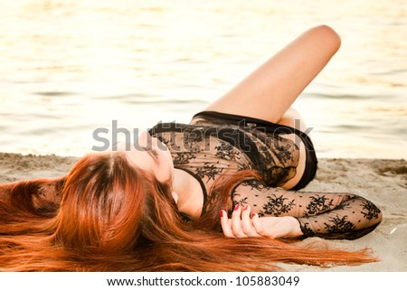 young redhead woman lie on sand beach summer day - stock photo