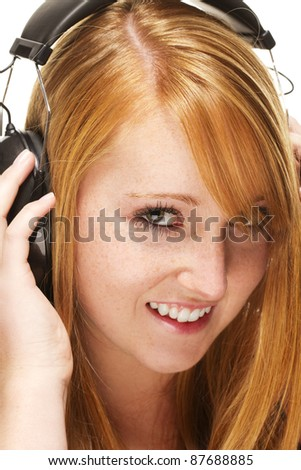 young redhead woman listening to music on white background - stock photo