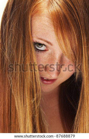 young redhead woman looking through her beautiful hair - stock photo