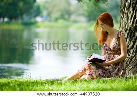 Young redhead woman studying in summer park - stock photo