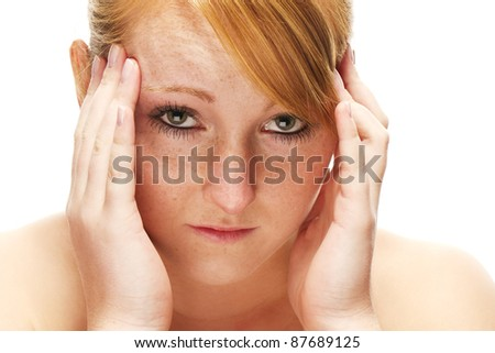 young redhead woman suffering on headache on white background - stock photo