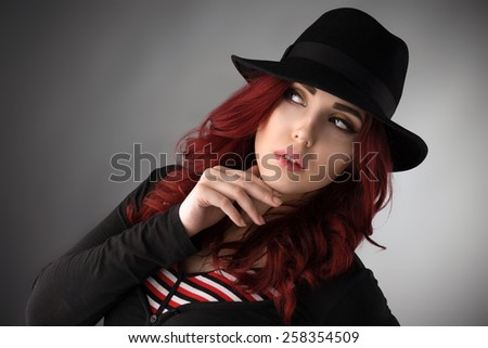 Young redhead woman wearing a hat and posing over gray studio background - stock photo