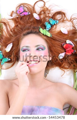 young redhead woman with butterflies and petals on her head lying biting her finger