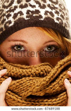young redhead woman with winter fashion hiding behind scarf - stock photo