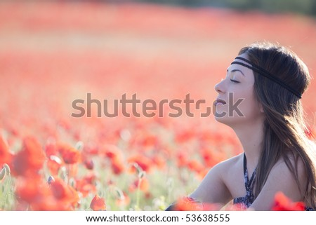 Young relaxed adult with closed eyes in a poppies field. - stock photo
