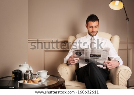 Young relaxed businessman reading newspaper sit on armchair. - stock photo