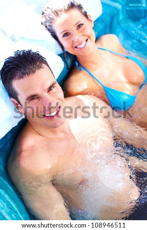 Young relaxed couple in jacuzzi. Spa. - stock photo