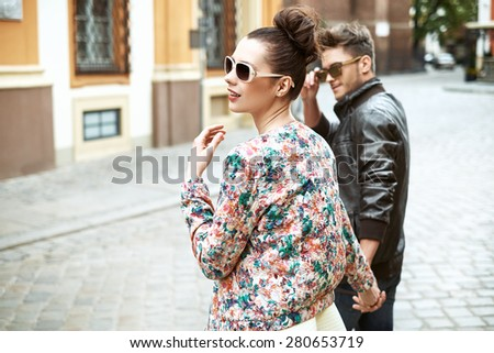 Young relaxed couple walking around the downtown - stock photo