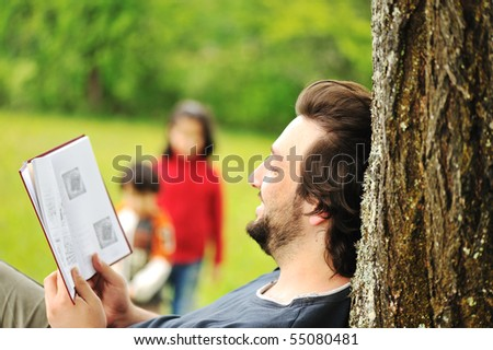 Young relaxed father reading book and children playing around - stock photo