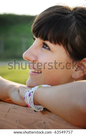 Young relaxed female sitting at a table and looking upwards at copyspace - stock photo
