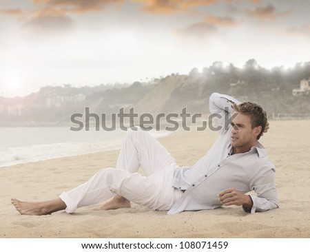 Young relaxed man laying on beach - stock photo