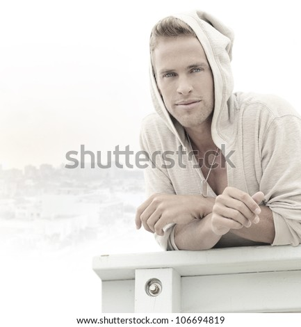 Young relaxed man outdoors in hooded shirt - stock photo