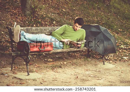 Young relaxed man reading book in nature  - stock photo