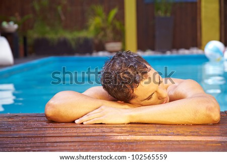 Young relaxed man resting on edge of swimming pool - stock photo