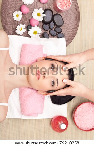 young relaxed woman receiving a head massage at spa center - stock photo