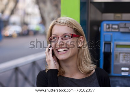 Young relaxed woman talking on the cell phone with the retro phone boot in the background. - stock photo
