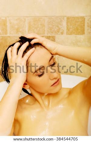 Young relaxing woman washing hair in bath  - stock photo