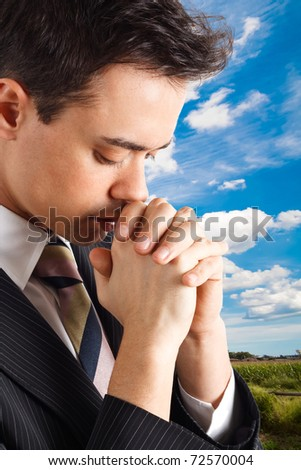 Young religious man praying outdoor. - stock photo