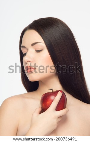 Young remarkable girl with unemotional face keeping red tasty apple and looking downward. Isolated on white background  - stock photo