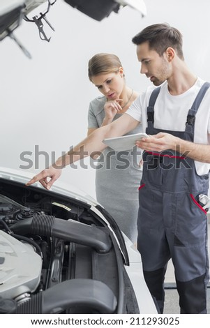 Young repair worker explaining car engine to worried customer in workshop - stock photo