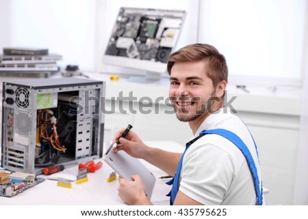 Young repairer working with screwdriver in service center