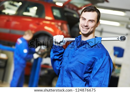 Young repairman auto mechanic inspecting car during automobile maintenance at engine auto repair shop service station - stock photo