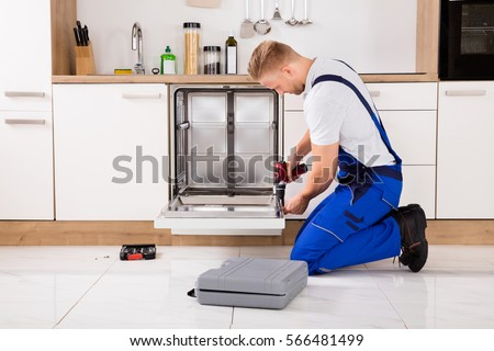 Young Repairman Service Worker Repairing Dishwasher Appliance In Kitchen