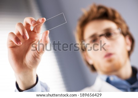 Young researcher holding a microscope glass slide in the laboratory. - stock photo