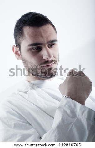Young researcher wearing a labcoat expressing satisfaction - stock photo