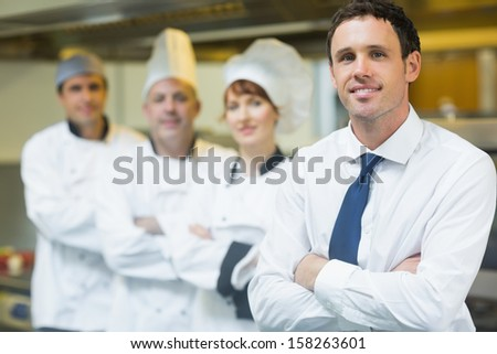Young restaurant manager posing in front of team in restaurant