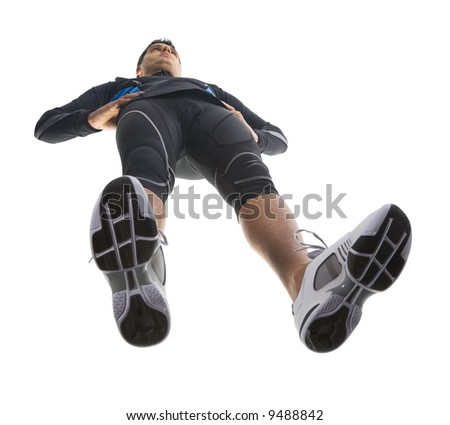Young, resting runner. Wearing tight-fitting uniform and standing straight. Low angle view - stock photo