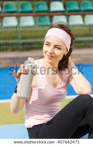 Young resting sportswoman holding bottle of water. Smiling girl sitting on the field after fitness workout  - stock photo