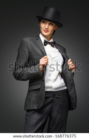 Young retro style business woman standing against grey background.  Woman feels like a man - concept. Woman wearing fashion suit and retro top hat posing against grey background.